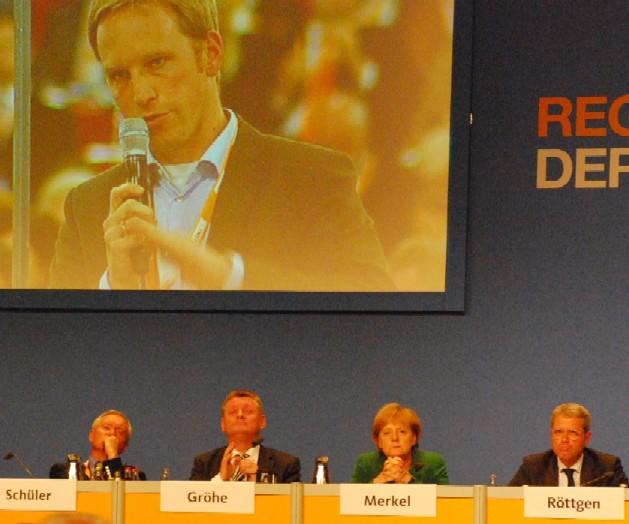 Bohrende Fragen an die Kanzlerin: CDU-Kreisvorsitzender Marc Henrichmann überlebensgroß über Angela Merkel bei der Regionalkonferenz.