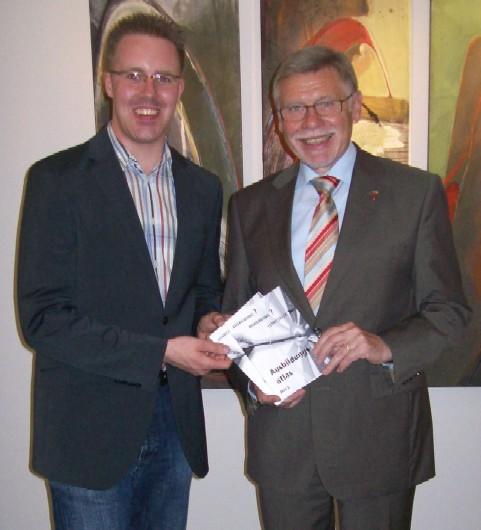 Der Kreisvorsitzende der Jungen Union Kreis Coesfeld, Christoph Wäsker, übergibt die ersten Exemplare des Ausbildungsatlas 2013 an Landrat Konrad Püning.