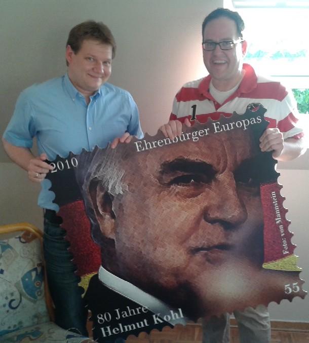 Sven Volmering (links) überreicht Henrik Bröckelmann die XXL-Gedenkmarke für Helmut Kohl.