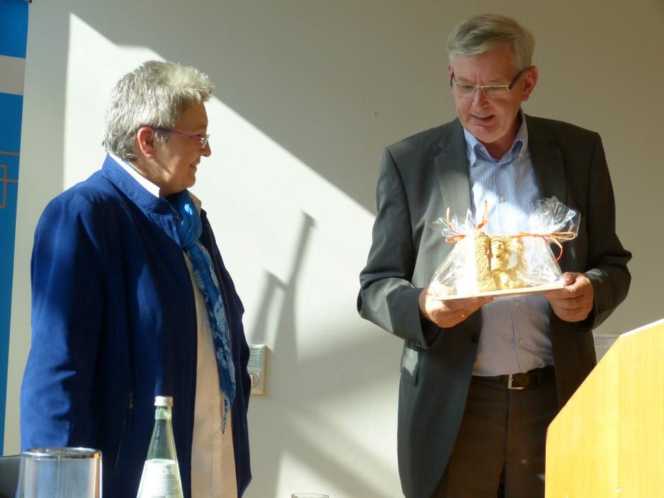 """MdB Karl Schiewerling überreicht Referentin Elke Hannack als Dankeschön das """"Coesfelder Heinzelmännchen"""" - einen """"Teitekerl"""" aus Sandstein."""